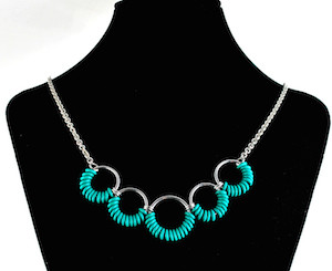 turquoise rubbermaille and aluminum simple coiled necklace on black neckform