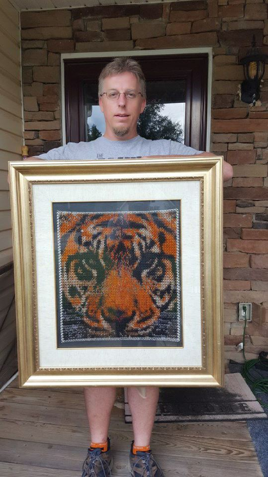 artist tony moeller holding framed chainmaille tiger inlay