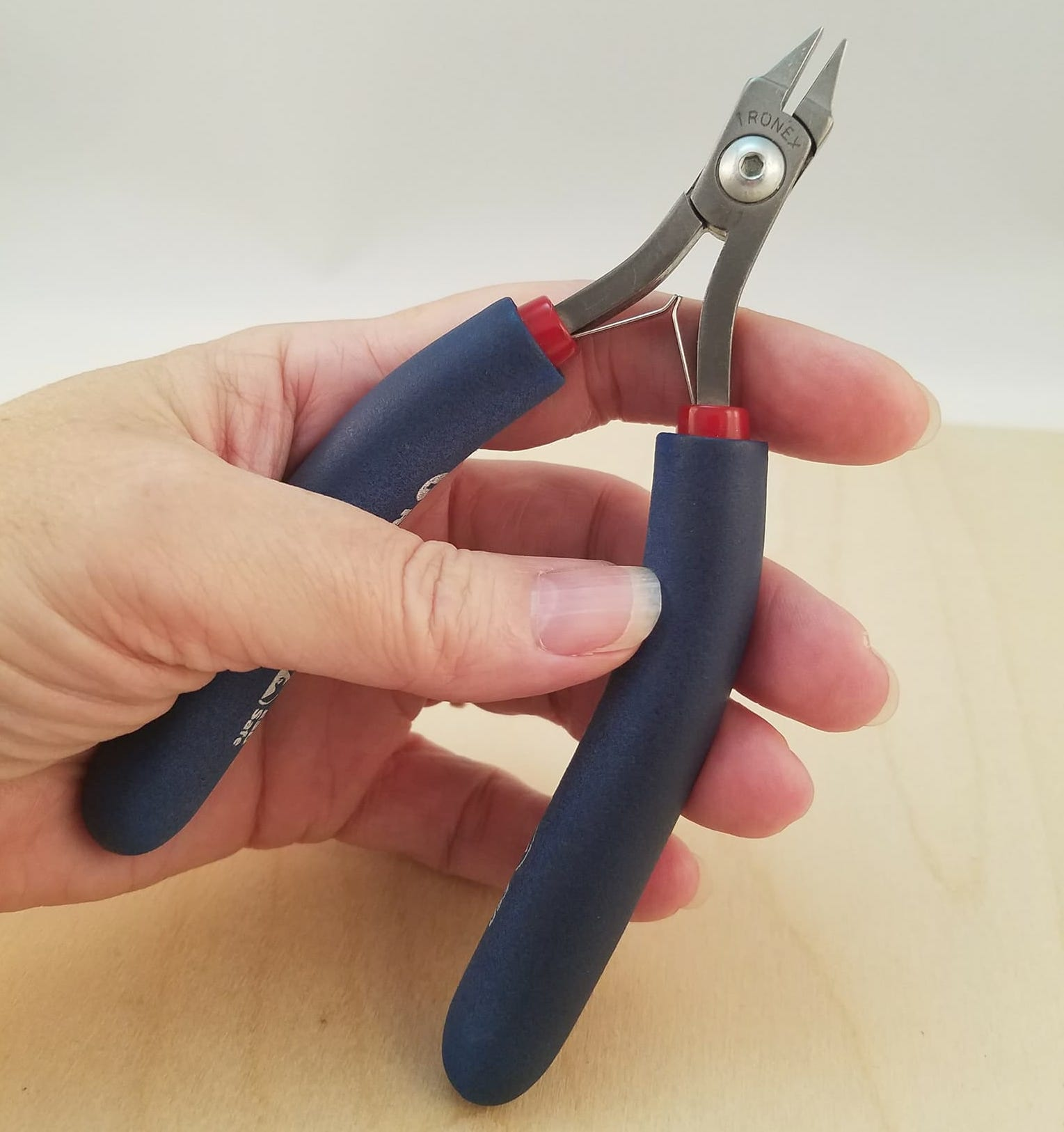 hand with tronex snub nose pliers