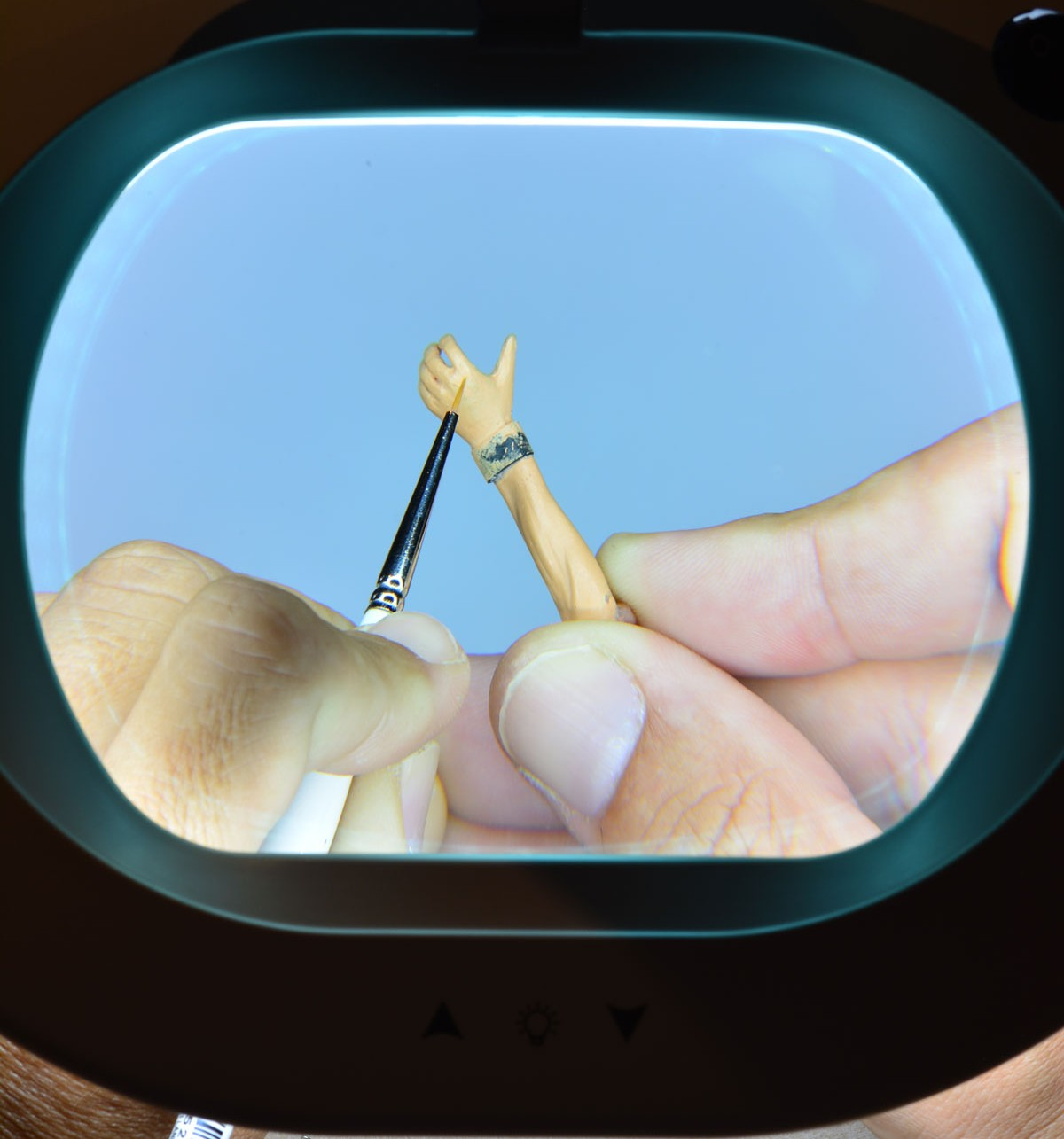 view through magnifier lamp showing small brush painting model hand