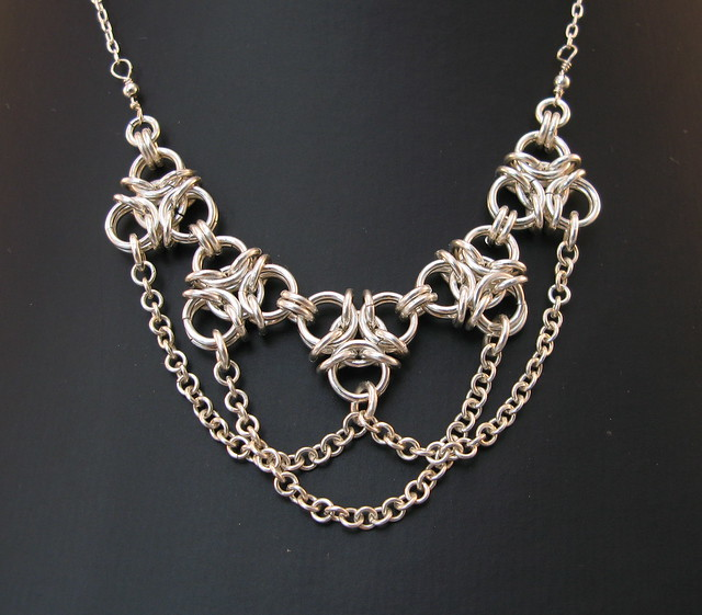 Aura2 chainmaille necklace in silver with draping chains on dark grey background