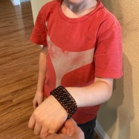 young boy holding up wrist with black chainmaille cuff