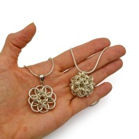 a palm holding two sterling silver chainmaille pendants