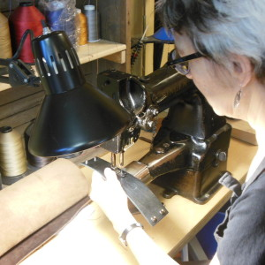 Sara of The Chicago School of Shoemaking working on a leather cuff.
