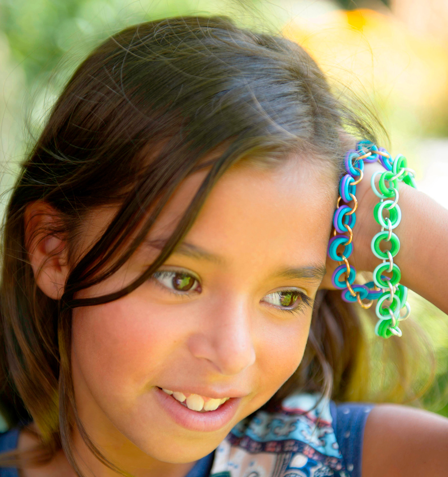Girl wearing friendship bracelets in blue, purple and green by Linkt Crafts Kits