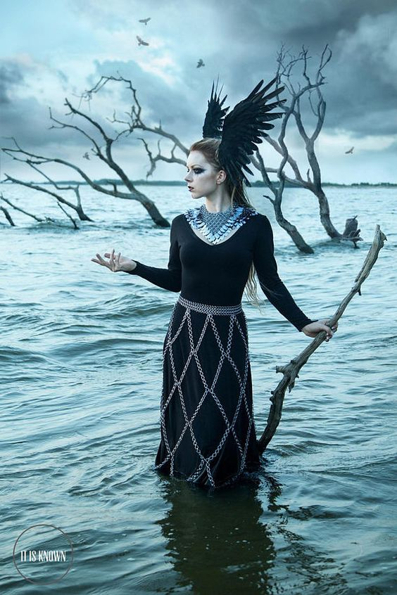 Woman in scalemaille collar and chainmaille skirt and winged headgear standing in water