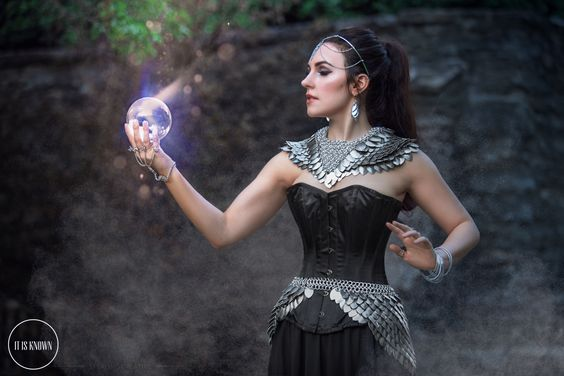 woman with scalemaille collar and bustle holding glowing orb