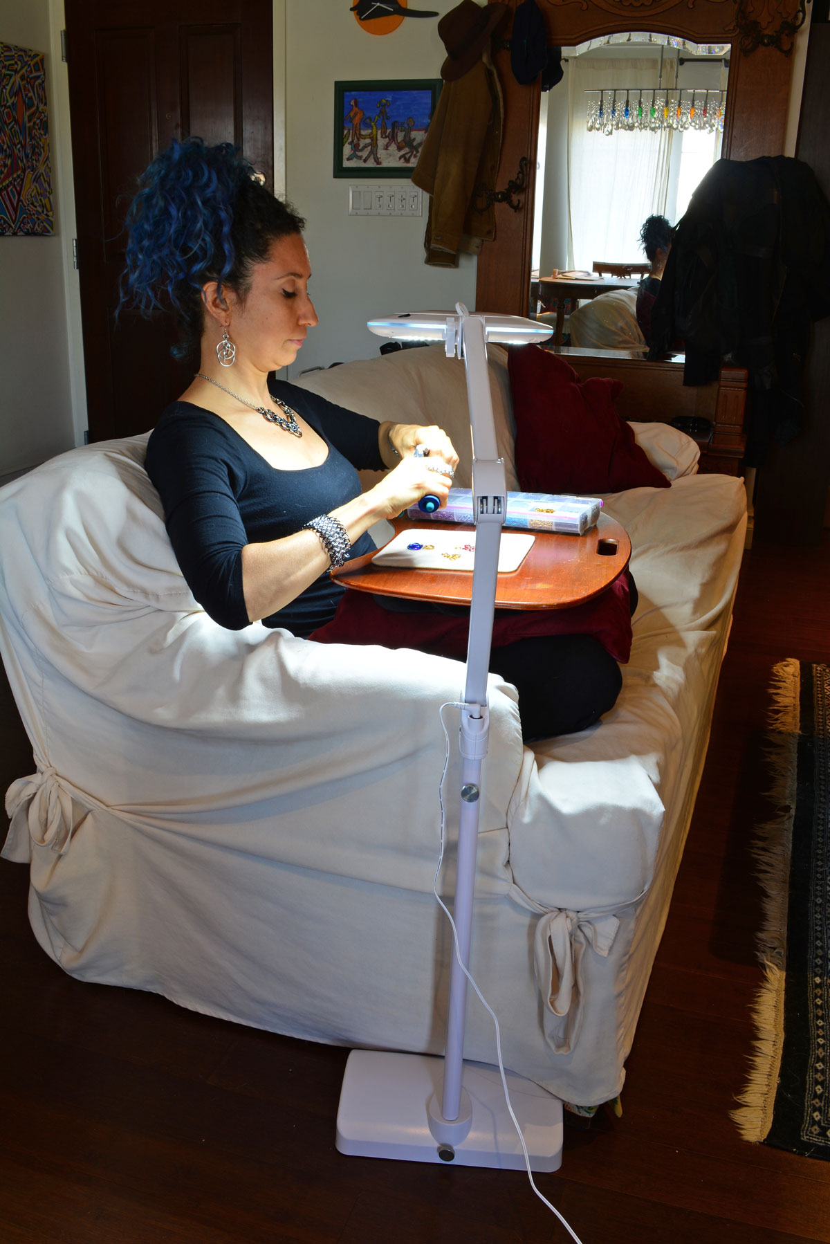crafter sitting on sofa making jewelry using brightech floor lamp