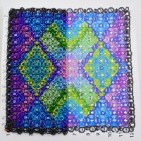 partially created chainmaille quilt square laid over a pattern guide