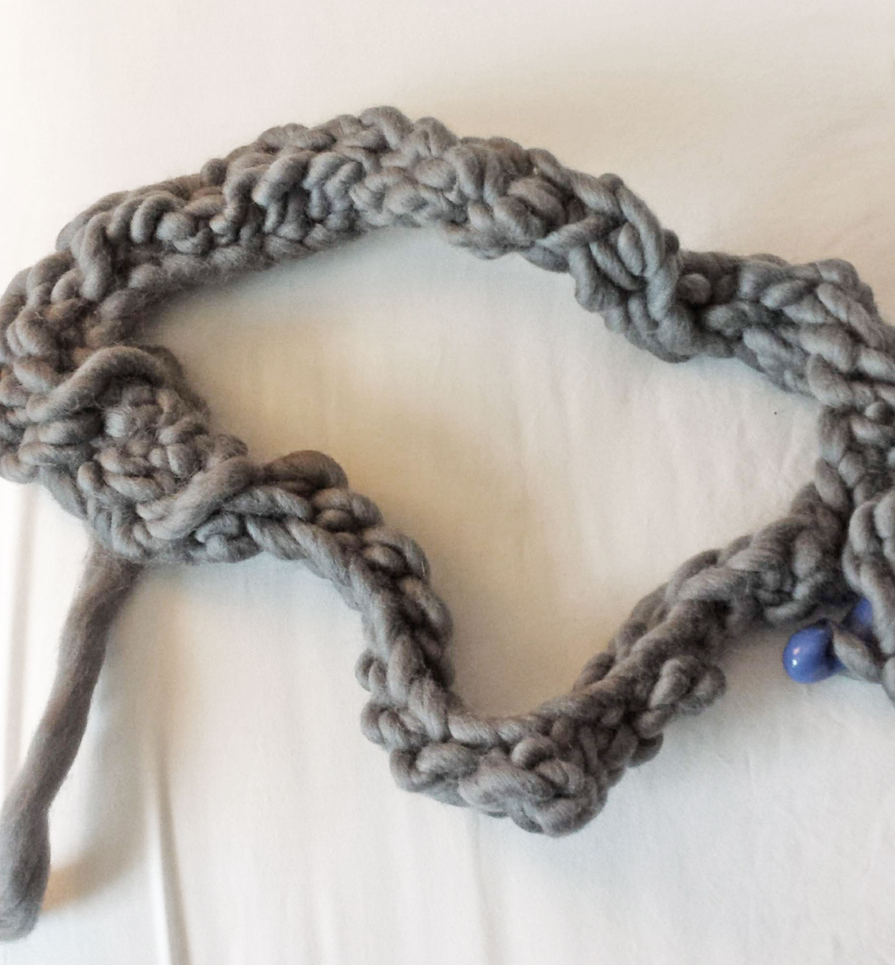tightly woven and knotted gnarly attempt at crochet made with thick gray yarn