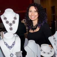 rebeca mojica standing next to her jewelry displays