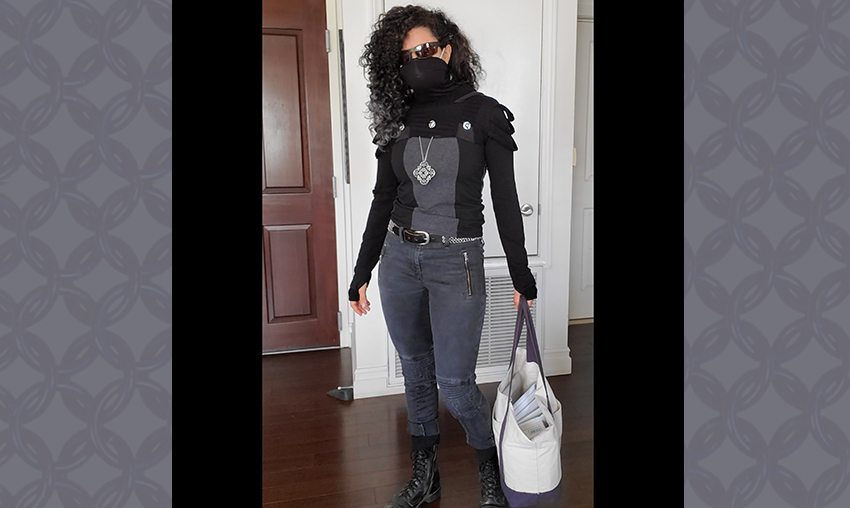 Rebeca wearing dystopian clothing with a black face mask and holding a bag of packages